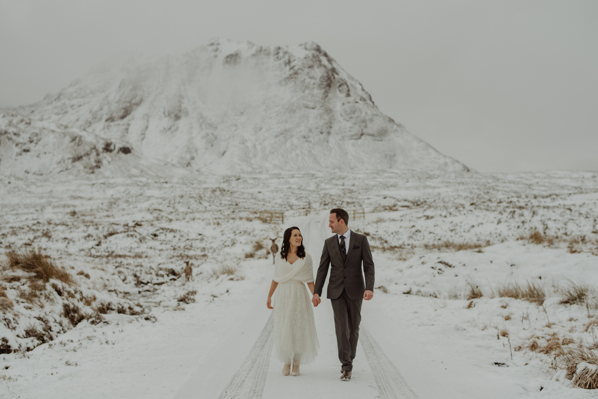 a wedding photograph of a couple walking through a snowy Glencoe in Scotland