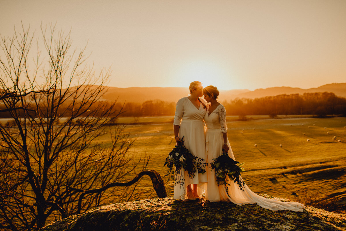 Two brides enjoy the sunset on their wedding day