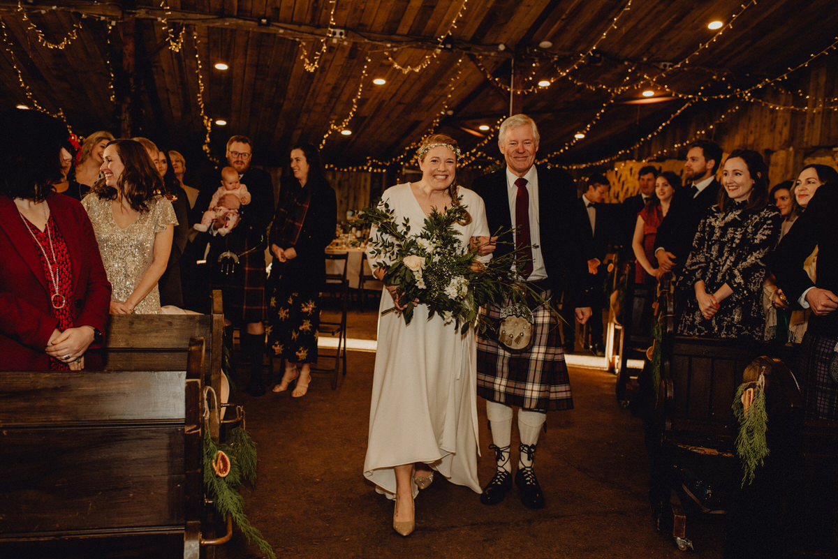 An excited bride walks down the aisle with her dad