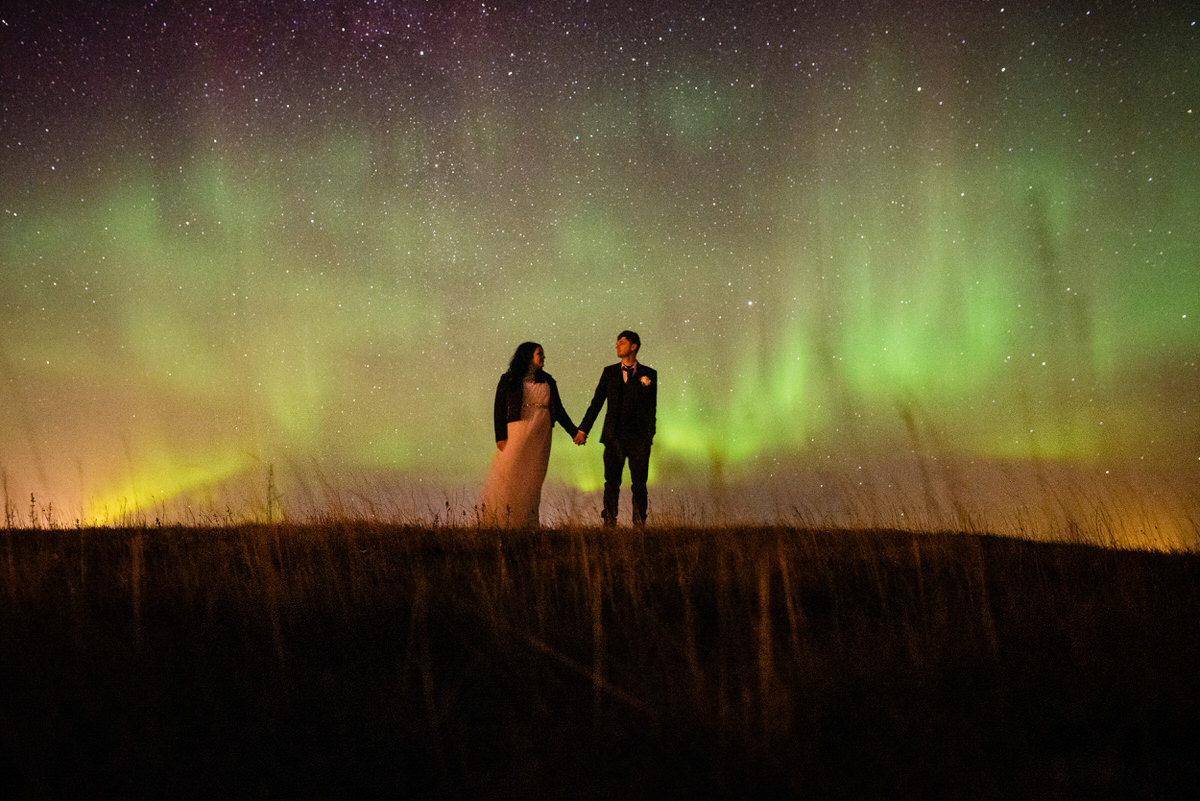 a wedding couple stand under the northern lights