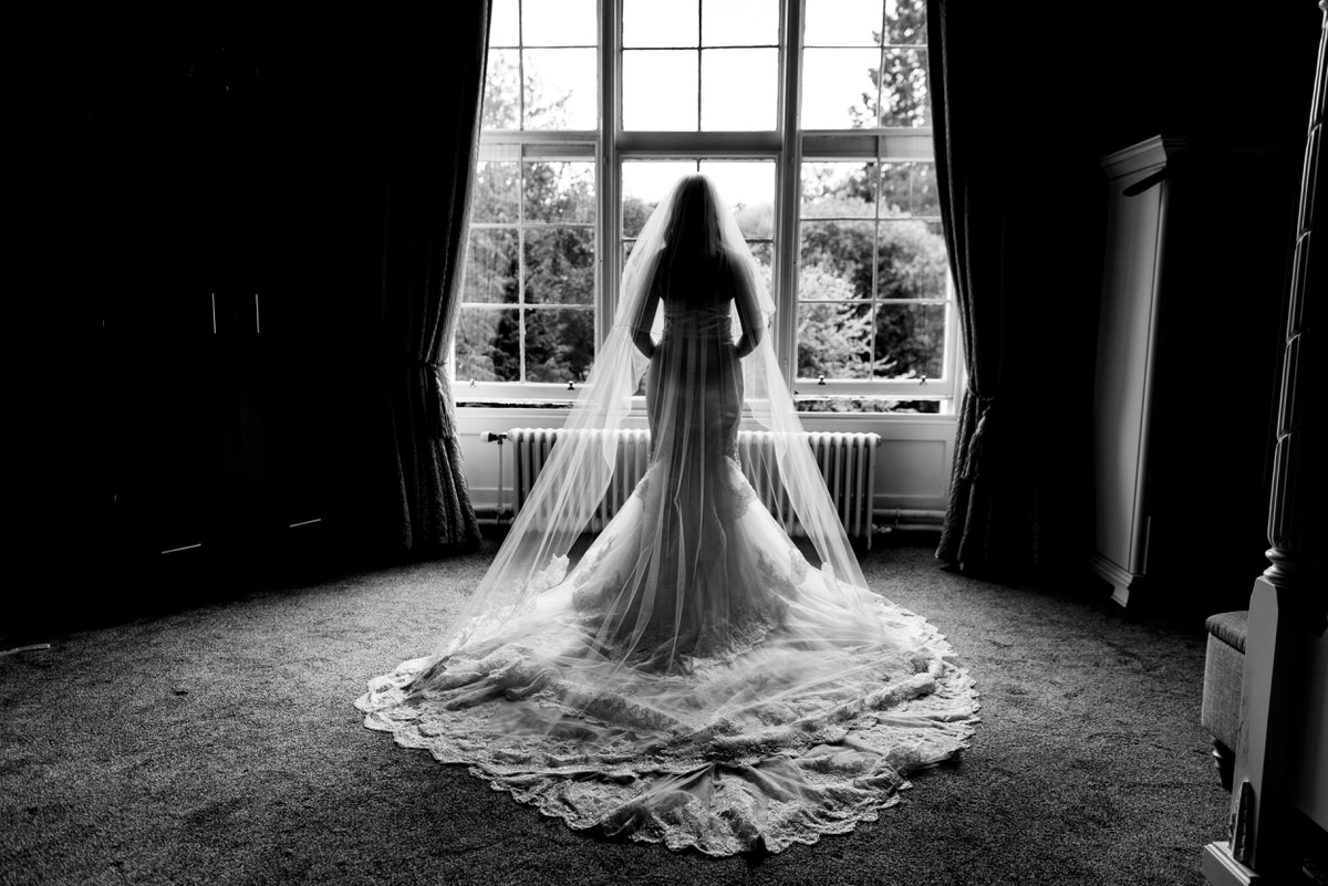 a bride in a beautiful dress stands by a window