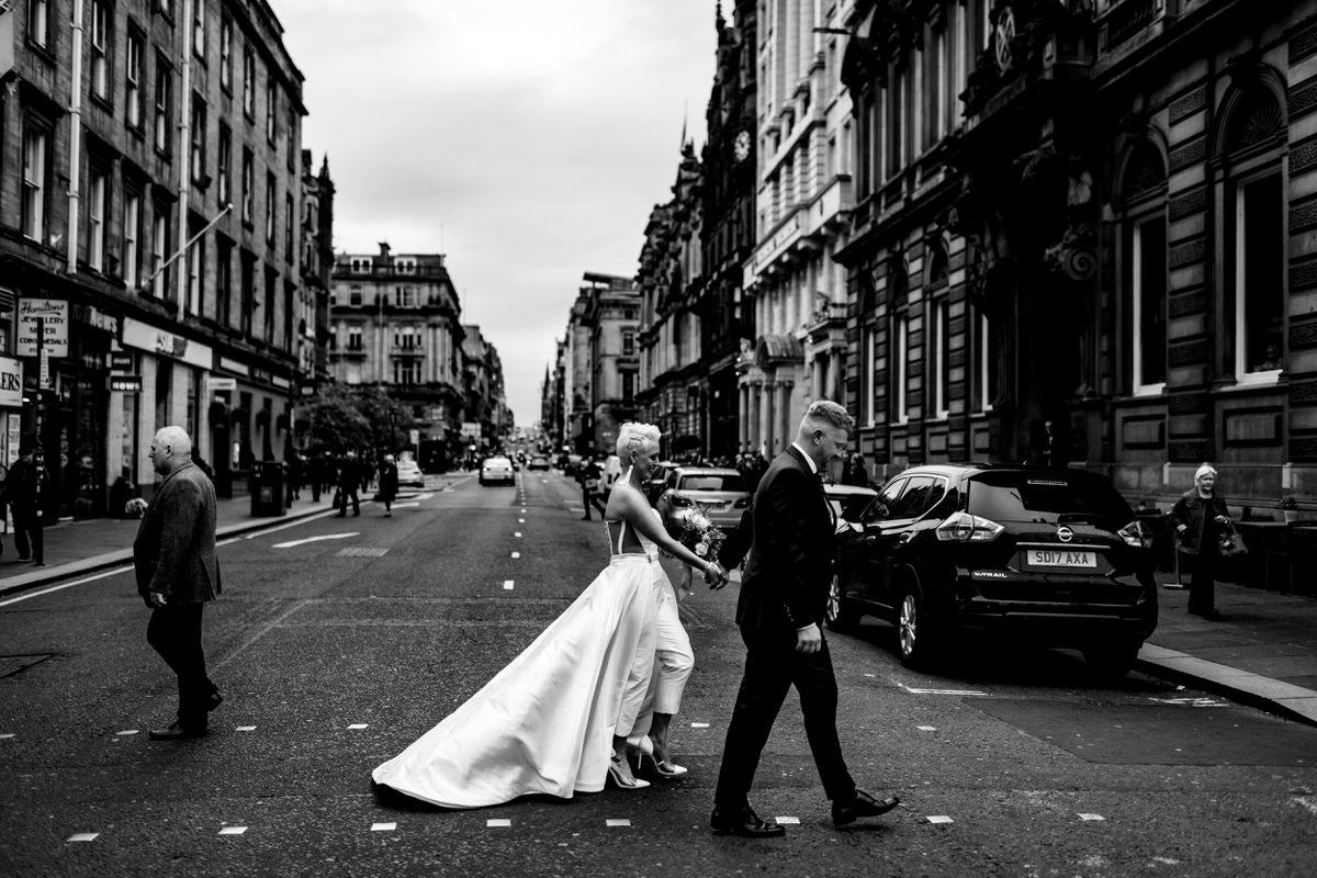 a wedding couple walk through Glasgow city centre