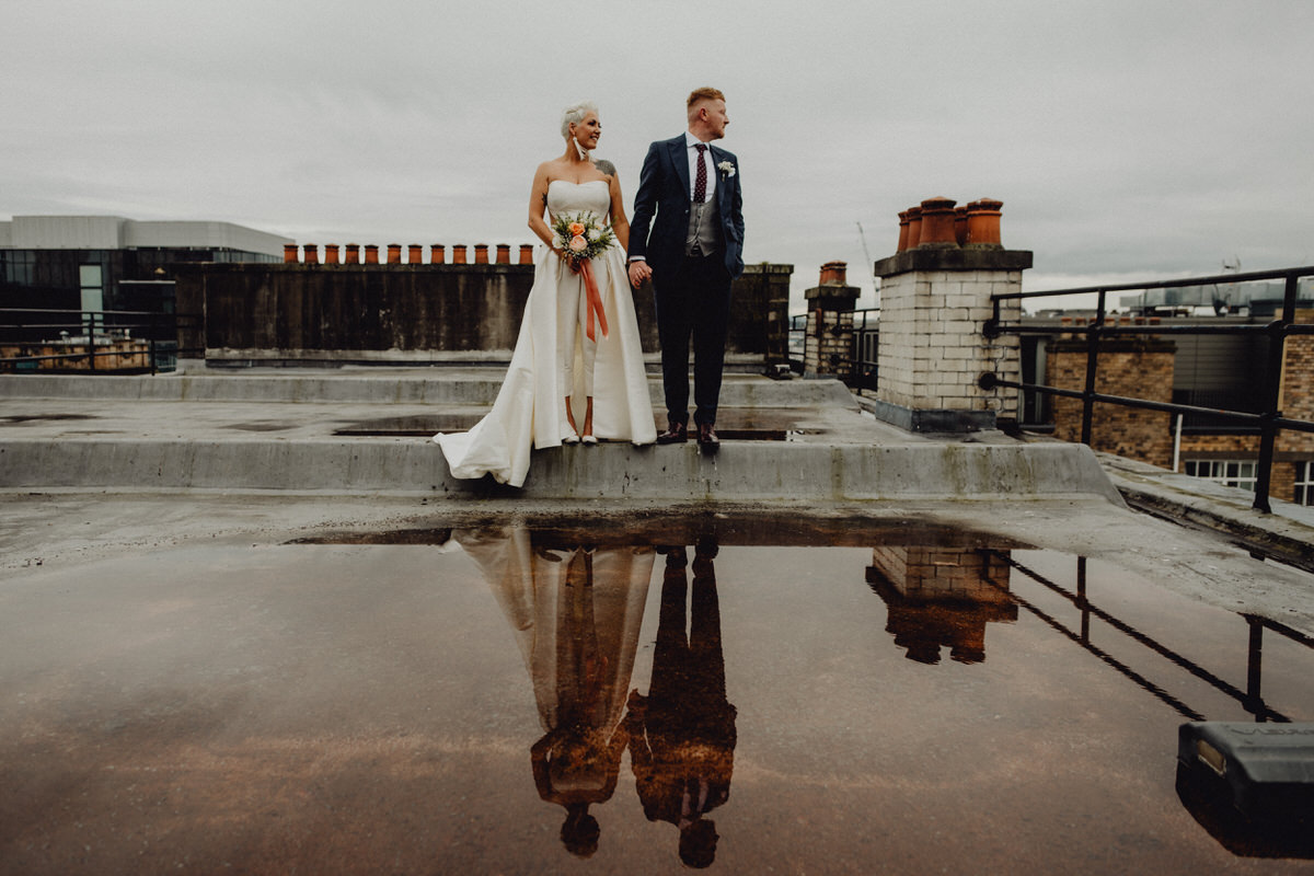 a wedding couple pose on a rooftop in Glasgow