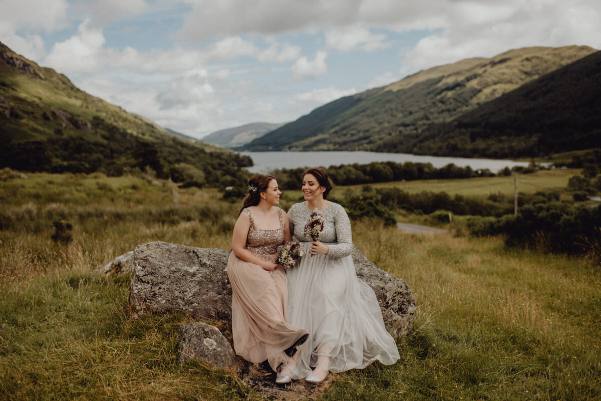 a wedding couple sit on a rock with views of a scottish loch in the background