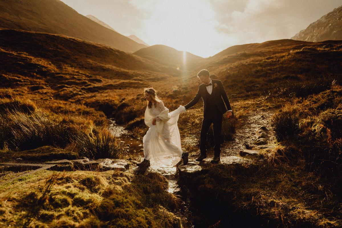A wedding couple make their way over a stream in Glencoe Scotland