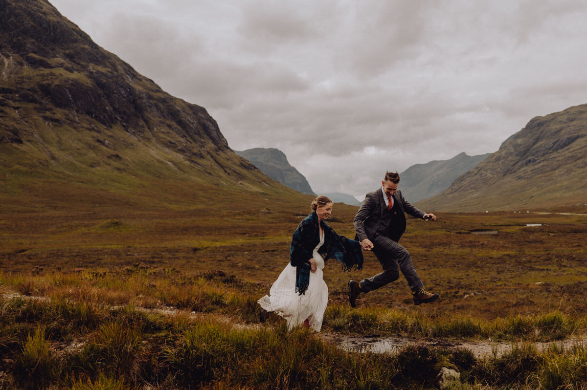 a wedding couple jump over a stream in Glencoe Scotland