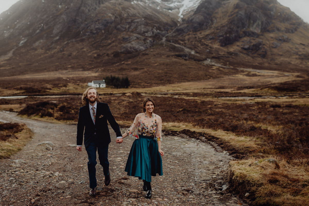 A wedding couple hold hands at Etive Mor in Glencoe Scotland